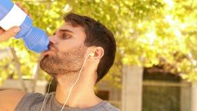 Stiligt dricksvatten för ung man under att jogga stock video