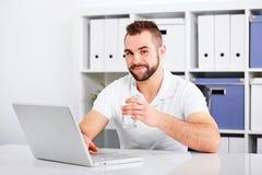 Stiligt dricksvatten för ung man från ett exponeringsglas Arkivbilder