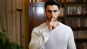 Stiligt göra för ung man hyssjar tecknet med fingret på kanter stock video