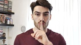 Stiligt göra för ung man hyssjar tecknet med fingret på kanter lager videofilmer