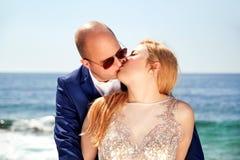 Stiligt gift paranseende och kyssa vid havet fotografering för bildbyråer