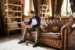 Stiligt grabbsammanträde på soffan med hans hund som spelar videospelet fotografering för bildbyråer
