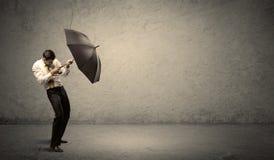 Stiligt hållande paraply för affärsman med kopieringsutrymmebackgroun Royaltyfri Bild