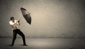 Stiligt hållande paraply för affärsman med kopieringsutrymmebackgroun arkivbild