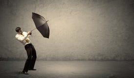 Stiligt hållande paraply för affärsman med kopieringsutrymmebackgroun arkivfoton