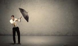 Stiligt hållande paraply för affärsman med kopieringsutrymmebackgroun royaltyfria foton
