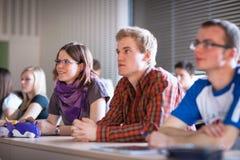 Stiligt högskolestudentsammanträde i ett klassrum Arkivfoto