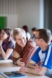 Stiligt högskolestudentsammanträde i ett klassrum mycket av studenter Royaltyfri Fotografi