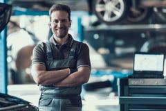 Stiligt le bilMachanic anseende i garage royaltyfria foton