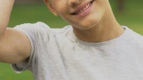 Stiligt le för tonårs- pojke som poserar för kamera, rengöringhud i tonårstid lager videofilmer