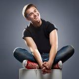 Stiligt le för ung man som isoleras över grå färger Royaltyfri Bild