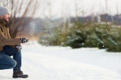 Stiligt le spela för ung man kastar snöboll fotografering för bildbyråer