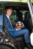 Stiligt lyckligt brudgumsammanträde i bil med buketten fotografering för bildbyråer