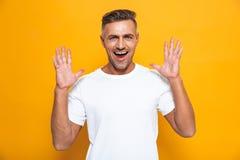 Stiligt lyckligt upphetsat posera för man som isoleras över gul väggbakgrund fotografering för bildbyråer