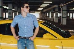Stiligt mananseende nära den moderna gula sportbilen Mode modernt annonsering Arkivfoton