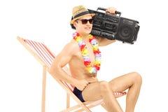 Stiligt manligt turist- koppla av på en stol med boombox på hans sh fotografering för bildbyråer
