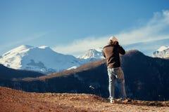 Stiligt manlopp i vinterberg med kameran arkivbilder