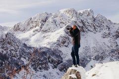 Stiligt manlopp i vinterberg med kameran royaltyfri bild