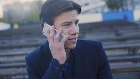 Stiligt mansammanträde på bänken och tala på smartphonen 4K arkivfilmer