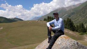 Stiligt mansammanträde på den stora stenen på bergdalen och landskap för gröna kullar lager videofilmer