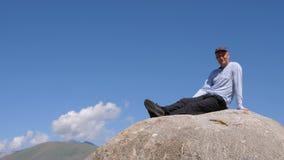 Stiligt mansammanträde på den stora stenen och se till kameran i bergtur lager videofilmer
