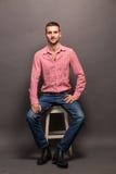 Stiligt mansammanträde på en stol i studio royaltyfria bilder
