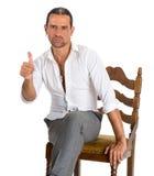 Stiligt mansammanträde på ett ok tecken för stol och för visning Royaltyfri Bild