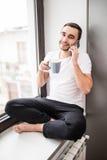Stiligt mansammanträde på fönsterbräda och kalla på telefon- och drinkkaffe i morgonen Royaltyfri Fotografi