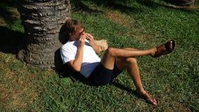 Stiligt mansammanträde på gräset i parkera under ett träd, läsebok, 4k, ultrarapid stock video