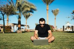 Stiligt mansammanträde på gräset och bruksbärbara datorn, chating eller läst internetnyheterna gömma i handflatan på bakgrund Som royaltyfri bild