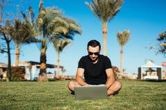 Stiligt mansammanträde på gräset och bruksbärbara datorn, chating eller läst internetnyheterna gömma i handflatan på bakgrund Som royaltyfri fotografi