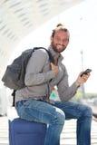 Stiligt mansammanträde på resväskan med den smarta telefonen royaltyfria foton