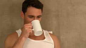 Stiligt mansammanträde på säng som dricker kaffe lager videofilmer