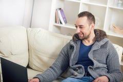 Stiligt mansammanträde på soffan med bärbara datorn arkivbilder