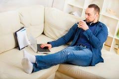 Stiligt mansammanträde på soffan med kopp te fotografering för bildbyråer