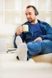 Stiligt mansammanträde på soffan med kopp te arkivfoto