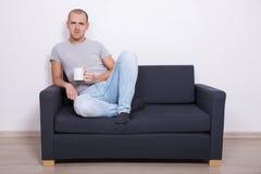 Stiligt mansammanträde på soffan och hållande ögonen på tv med kopp te royaltyfria bilder