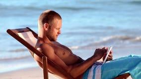 Stiligt mansammanträde på stranden stock video