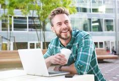 Stiligt mansammanträde utomhus med bärbara datorn och kaffe royaltyfria foton