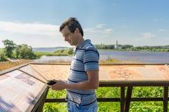 Stiligt medelålderst turist- mananseende nära informativ boa arkivbild