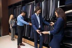 Stiligt mode för affärsmannen och kvinnashoppar, kunder som väljer kläder i detaljist fotografering för bildbyråer