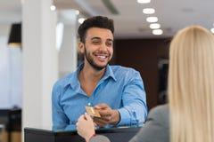 Stiligt mode för affärsmannen shoppar, kunden ger kreditkortbetalning i detaljisten, kvinnaportionklient royaltyfria foton