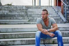 Stiligt muskulöst blont mansammanträde på trappamoment fotografering för bildbyråer