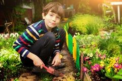 Stiligt pojkearbete för Preteen i trädgården royaltyfri bild
