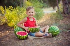 Stiligt pojkebarn som poserar i Central Park skogäng med den nya saftiga röda gröna vattenmelon för sommar med plast- coctailsugr Royaltyfri Bild