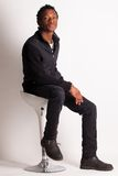 Stiligt sammanträde för svart grabb på en stol royaltyfria foton