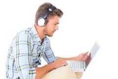 Stiligt sammanträde för ung man genom att använda bärbara datorn arkivbilder