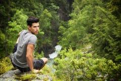 Stiligt sammanträde för ung man i frodigt grönt berg arkivbild