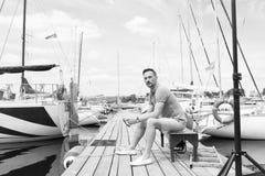 Stiligt sammanträde för ung man på bänk i skeppsdockan av fjärden mellan fartyg Allvarlig fartygman på pir som bort ser royaltyfria bilder
