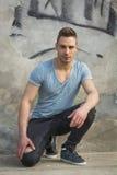 Stiligt sammanträde för ung man på betong med riven sönder jeans royaltyfri bild